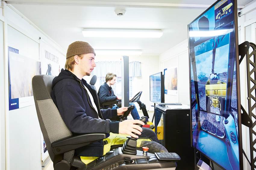 Eleverna Linus Lundgren och Viktor Forselius i arbete i simulatorerna som Rekarnegymnasiet i Eskilstuna köpte från Volvo Construction Equipment.