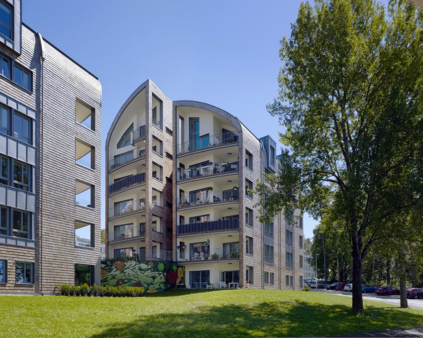 Våren 2015 stod 44 nya lägenheter klara vid Åsbovägen 12 och 14 i Fristad utanför Borås. Då hade det gått 24 år sedan den senaste nyproduktionen för det lilla allmännyttiga bostadsbolaget Fristadbostäder, Fribo. De två nya husen vid Åsbo-vägen har inte bara trästomme – träet är närvarande också i den cederspånklädda fasaden och i lägenheternas ytskikt där träet lämnats synligt.
