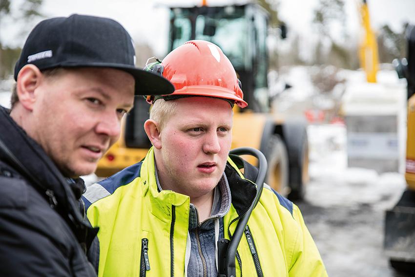 Torbjörn Eriksson instruerar Marcus Öman hur fjärrstyrningen på Huddigs grävlastare fungerar.