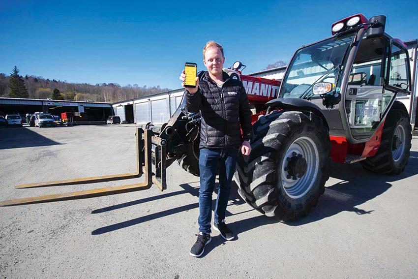 Mathias Tranby, vd på anläggningsföretaget Tranby AS i Oslo, håller upp en mobiltelefon med SmartDok-appen. I bakgrunden ser vi en av många maskiner företaget har i drift.