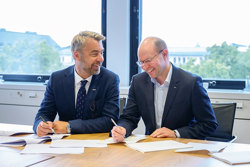 Fr v: Jesper Göransson, vd och koncernchef Peab och Kari Kauniskangas, vd och koncernchef YIT, signerar avtalet. Foto: Jyri Laitinen